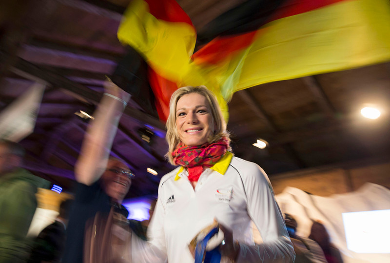 . Germany\'s Maria Hoefl-Riesch arrives with her gold and silver medals at the German house at the 2014 Winter Olympics, Saturday, Feb. 15, 2014, in Krasnaya Polyana, Russia. Hoefl-Riesch finished second in the women\'s super-G after taking the gold medal in the super combined five days earlier. (AP Photo/Gero Breloer)