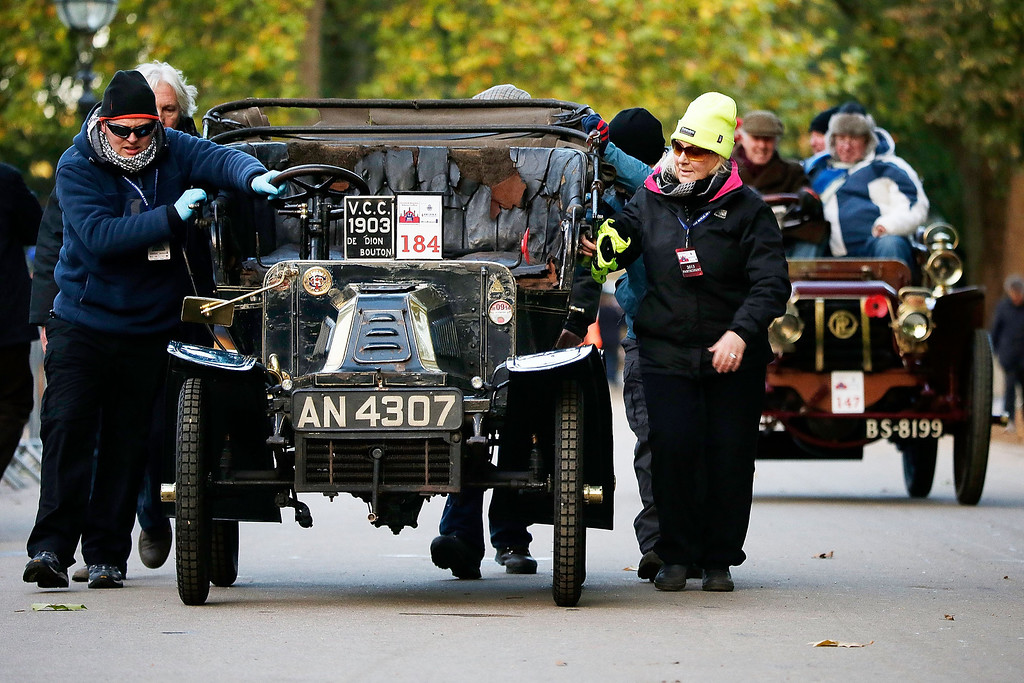 . Participants push a car to the start of the Royal Automobile Club\'s annual Veteran Car Run in Hyde Park on November 3, 2013 in London, England. Around 500 eligible pre-1905 cars take part in The Royal Automobile Club\'s annual 60-mile drive from Hyde Park in central London to the seafront on the Sussex resort of Brighton. It is the longest running motoring event in the world, and attracts entrants from across the globe.  (Photo by Matthew Lloyd/Getty Images)
