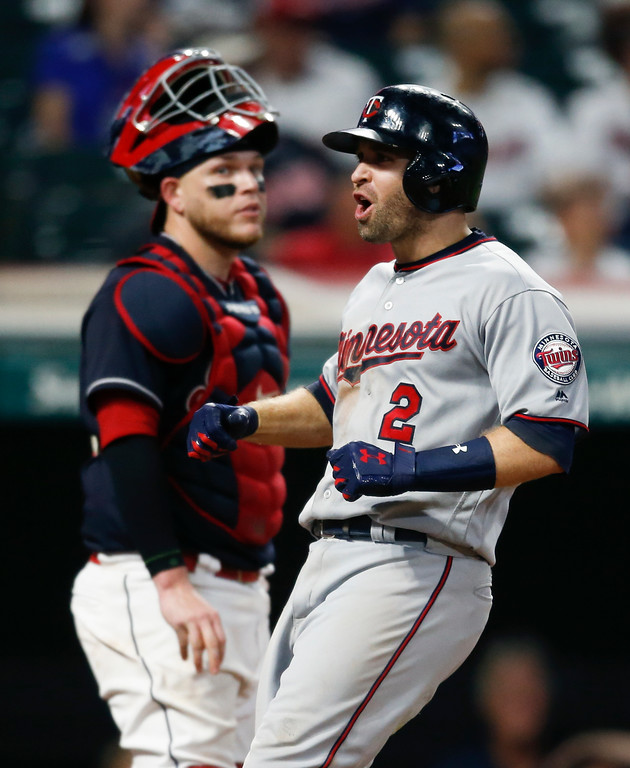. Minnesota Twins\' Brian Dozier (2) celebrates after hitting a three run home run off Cleveland Indians relief pitcher Bryan Shaw as catcher Roberto Perez looks on during the eighth inning in a baseball game, Tuesday, Sept. 26, 2017, in Cleveland. (AP Photo/Ron Schwane)