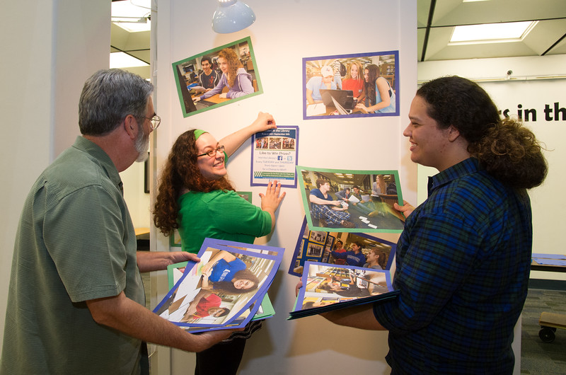 """Library media specialist Jeffrey Janko(left), Patricia Hernandez and Joe Hernandez prepare for the """"Islander in the Library"""" event which take place during August 3rd to september 15th in Mary and Jeff Bell Library."""