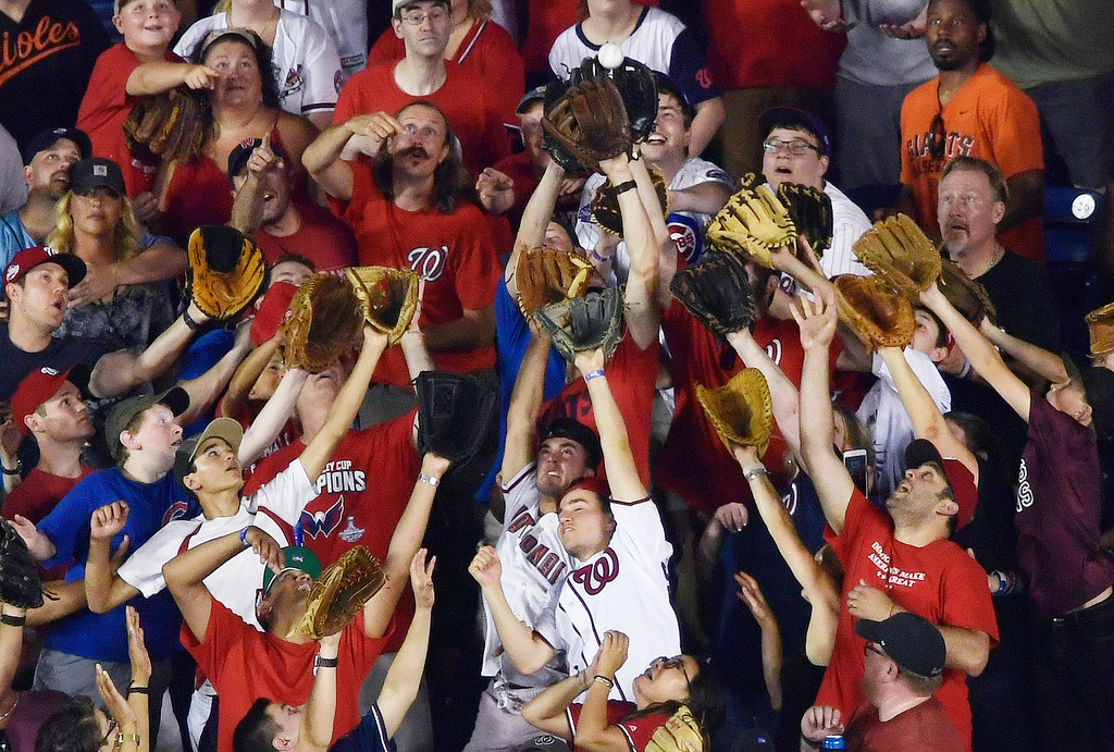 . Fans reach for a home run ball during the MLB Home Run Derby, at Nationals Park, Monday, July 16, 2018 in Washington. The 89th MLB baseball All-Star Game will be played Tuesday. (AP Photo/Susan Walsh)