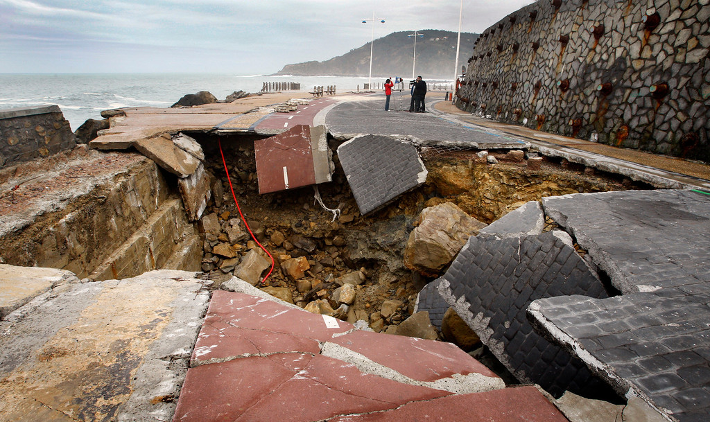 . Members of a television crew stand near a hole in the Paseo Nuevo in San Sebastian March 12, 2008. The hole was caused by a storm on Thursday that sunk numerous boats and caused extensive damage in the Biscay area. REUTERS/Vincent West (SPAIN)