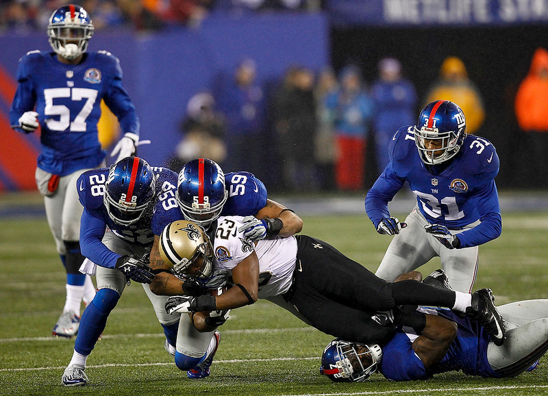 . Jayron Hosley #28 and Michael Boley #59 of the New York Giants tackle Pierre Thomas #23 of the New Orleans Saints  during their game at MetLife Stadium on December 9, 2012 in East Rutherford, New Jersey.  (Photo by Jeff Zelevansky/Getty Images)