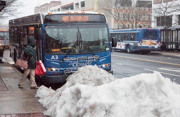 03/21/18 Wesley Bunnell   Staff A CT Transit passenger prepares to cross the street during the beginning of snow flurries to catch her bus on Wednesday evening with the remnants of past storms still visible. The expected nor'easter started late in the day after many businesses and schools closed early for the day.