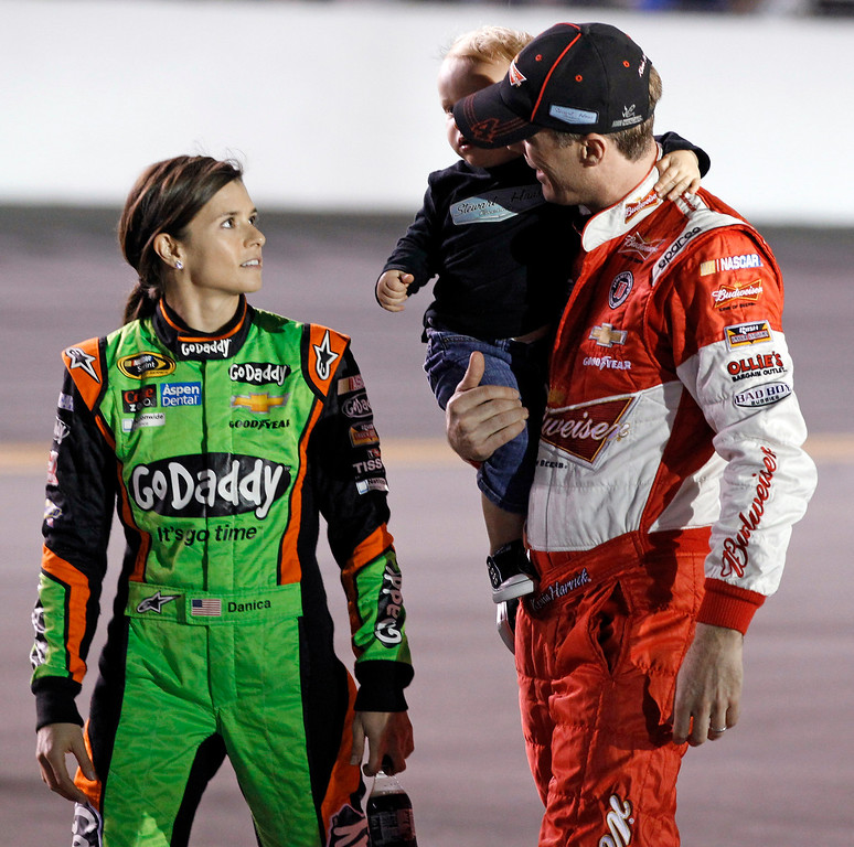 . Danica Patrick, left, talks with Kevin Harvick before the first of two NASCAR Sprint Cup series qualifying auto races in Daytona Beach, Fla., Thursday, Feb. 20, 2014. (AP Photo/Terry Renna)