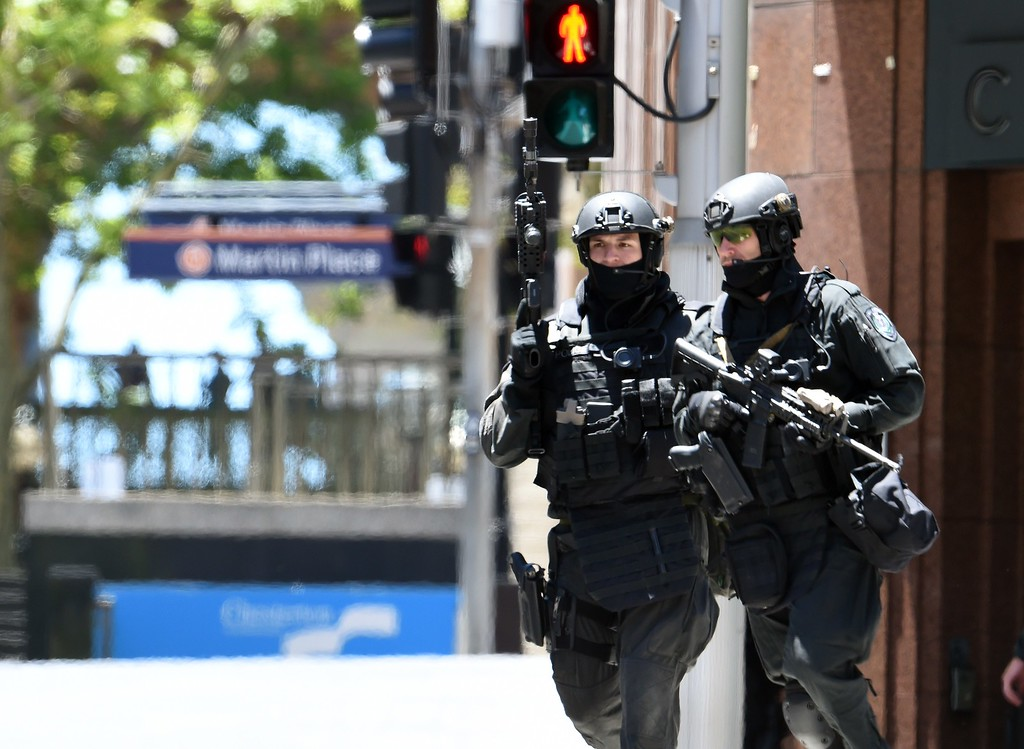". Armed police are seen outside a cafe in the central business district of Sydney on December 15, 2014. Hostages were being held inside a cafe in central Sydney on December 15 with an Islamic flag displayed against a window, according to witnesses and reports, while police said they were also responding to an ""incident\"" at the nearby Opera House. SAEED KHAN/AFP/Getty Images"