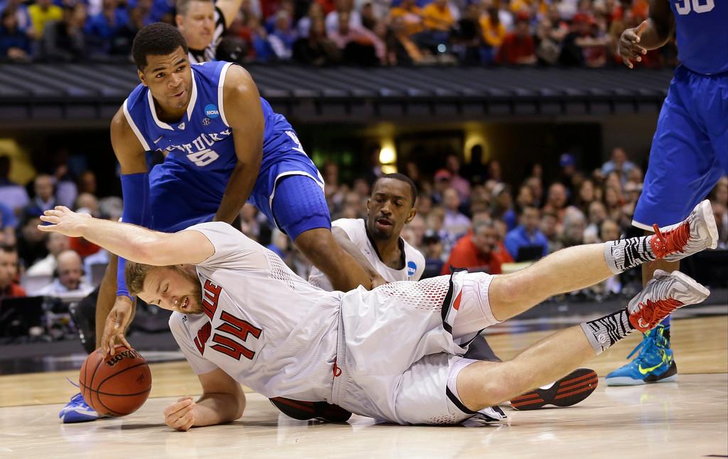 . Louisville\'s Stephan Van Treese (44) and Kentucky\'s Andrew Harrison (5) go after a loose ball during the second half of an NCAA Midwest Regional semifinal college basketball tournament game Friday, March 28, 2014, in Indianapolis. (AP Photo/Michael Conroy)