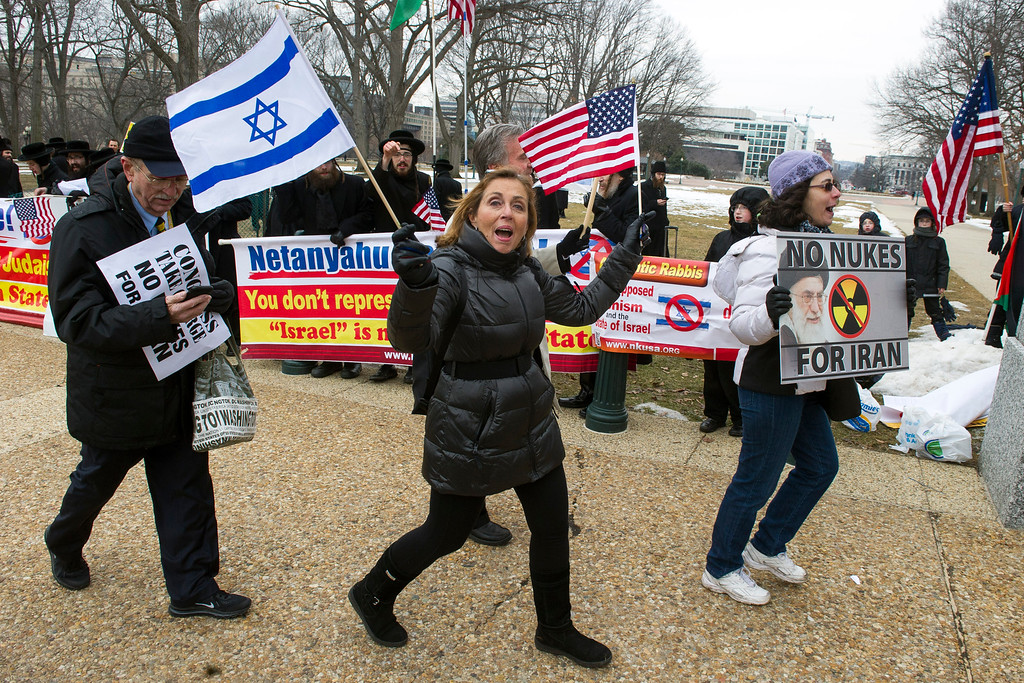 . Pro Israel demonstrators walks past anti-Israel demonstrators on Capitol Hill in Washington, Tuesday, March 3,2015, while Israeli Prime Minister Benjamin Netanyahu addressed a joint meeting of Congress. (AP Photo/Cliff Owen)