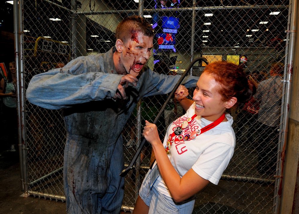 . Olivia D\'Agostino pulls a away from a zombie at AMC\'s Walking Dead booth during the Preview Night event on Day 1 of the 2013 Comic-Con International Convention on Wednesday, July 17, 2013 in San Diego. (Photo by Denis Poroy/Invision/AP)