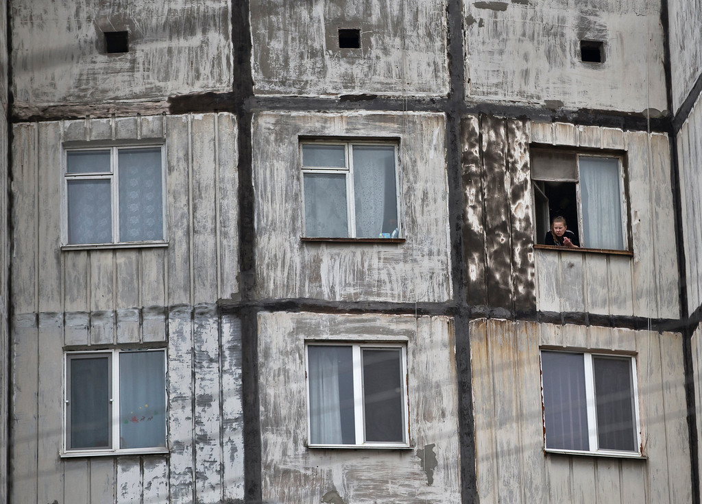 """. A woman smokes by the window in an apartment block in Simferopol, Ukraine, Tuesday, March 11, 2014. Crimea\'s regional legislature on Tuesday adopted a \""""declaration of independence of the Autonomous Republic of Crimea.\"""" The document specified that Crimea will become an independent state if its residents vote on Sunday in favor of joining Russia in the referendum.(AP Photo/Vadim Ghirda)"""