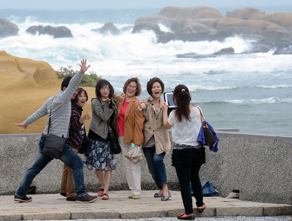 . Tourists pose for pictures at Hoping island, in Keelung, northern Taiwan as typhoon Fitow approaches on October 5, 2013. Taiwan on October 5 issued a warning over Typhoon Fitow as it approached the island\'s north with threats of torrential rains and powerful winds over the weekend.   SAM YEH/AFP/Getty Images