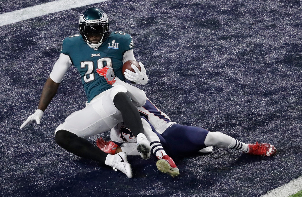 . Philadelphia Eagles running back LeGarrette Blount, left, scores past New England Patriots strong safety Duron Harmon during the first half of the NFL Super Bowl 52 football game Sunday, Feb. 4, 2018, in Minneapolis.(AP Photo/Eric Gay)