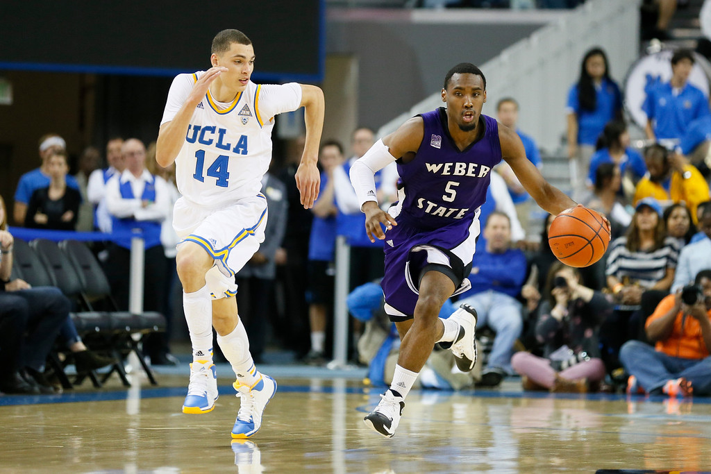 . Weber State\'s Jordan Richardson dribbles the ball as UCLA\'s Zach LaVine, left, runs back to defend during the first half of an NCAA college basketball game, Sunday, Dec. 22, 2013, in Los Angeles. (AP Photo/Danny Moloshok)