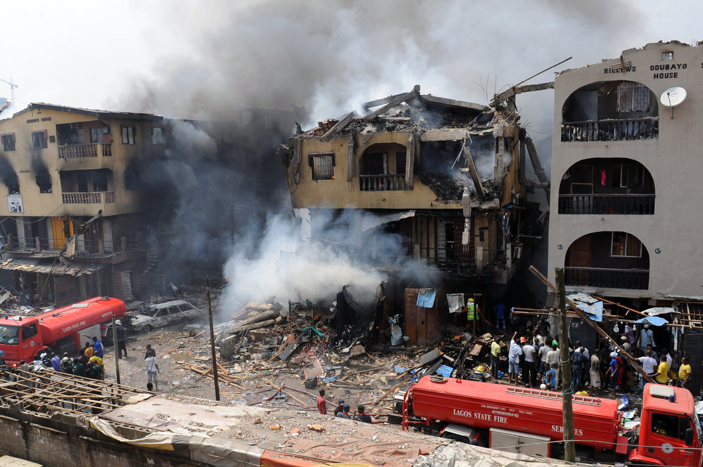 Description of . Smoke billows from a building after an explosion in Lagos on December 26, 2012.  Fire ripped through a crowded neighborhood in Nigeria\'s largest city and wounded at least 30 people after a huge explosion rocked a building believed to be storing fireworks, officials said.  AFP PHOTO/PIUS  UTOMI EKPEI/AFP/Getty Images