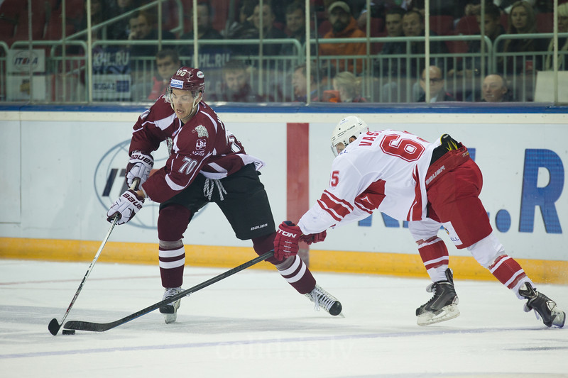 Alexander Vasilyev (65) tries to take the puck away from Miks Indrasis (70)