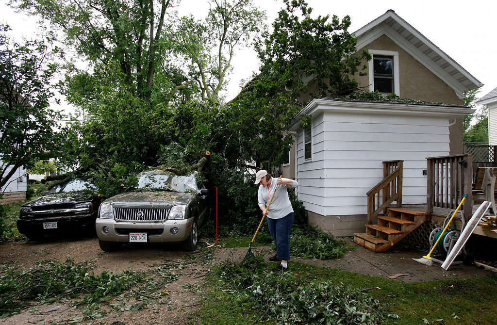 . Alex Beck clears debris at her parents\' house in Hortonville, Wis. (AP Photo/The Post-Crescent, Sharon Cekada)