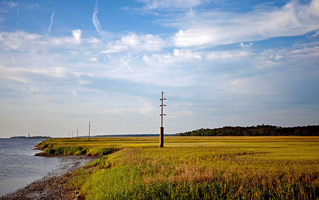 . A utility pole stands in a marsh at sunset on Sapelo Island, Ga. on Thursday, May 16, 2013. (AP Photo/David Goldman)