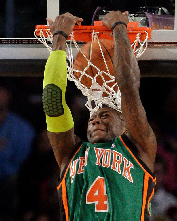 . New York Knicks\' Nate Robinson dunks over his head in the slam dunk event during the NBA All-Star Weekend basketball, Saturday, Feb. 14, 2009, in Phoenix. (AP Photo/Ross D. Franklin)