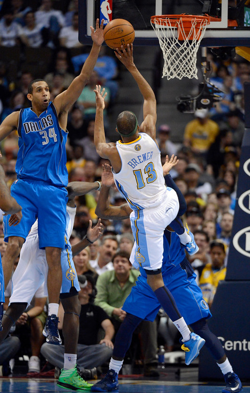 . DENVER, CO. - APRIL 04: Corey Brewer (13) of the Denver Nuggets takes an off balance shot over Brandan Wright (34) of the Dallas Mavericks during the fourth quarter April 4,  2013 at Pepsi Center. (Photo By John Leyba/The Denver Post)