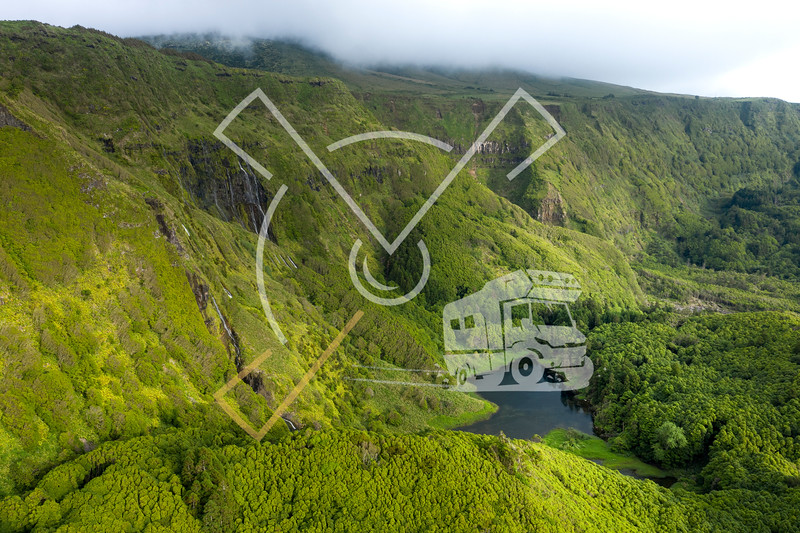 aerial landscape image of sunset sunrise over Poço Ribeira do Ferreiro waterfalls and Lagoa dos Patos with its remarkable amazing tropical like green vegetation and forests at the Ilha das Flores island on the Azores