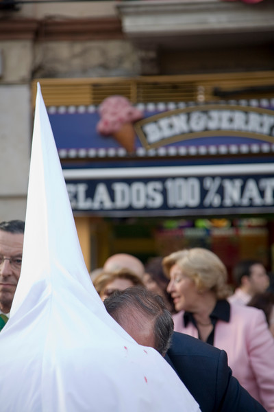 The pointed hood of a penitent in front of an ice-cream parlor, Holy Week 2008, Seville, Spain