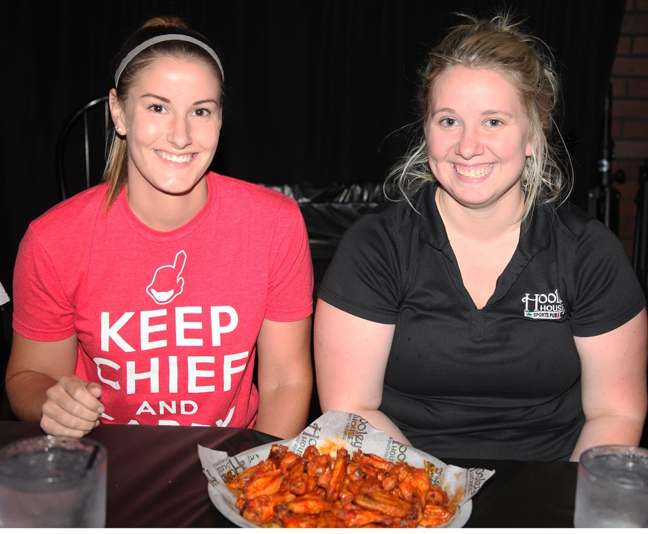 . Hooley House general manager Megan McKinney (right) and shift manager Carmen Rix take on the football players in round two of Tuesday\'s wing eating contest.