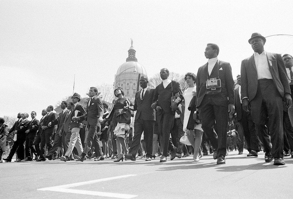 . The vanguard of people who will walk Dr. Martin Luther King, Jr.\'s funeral procession route pass Georgia\'s gold-domed Capitol building in Atlanta, April 9, 1968, before church services for Dr. King were completed.  The march began early in an attempt to clear the church area enough to get the mule-drawn caisson to the doors.  (AP Photo)