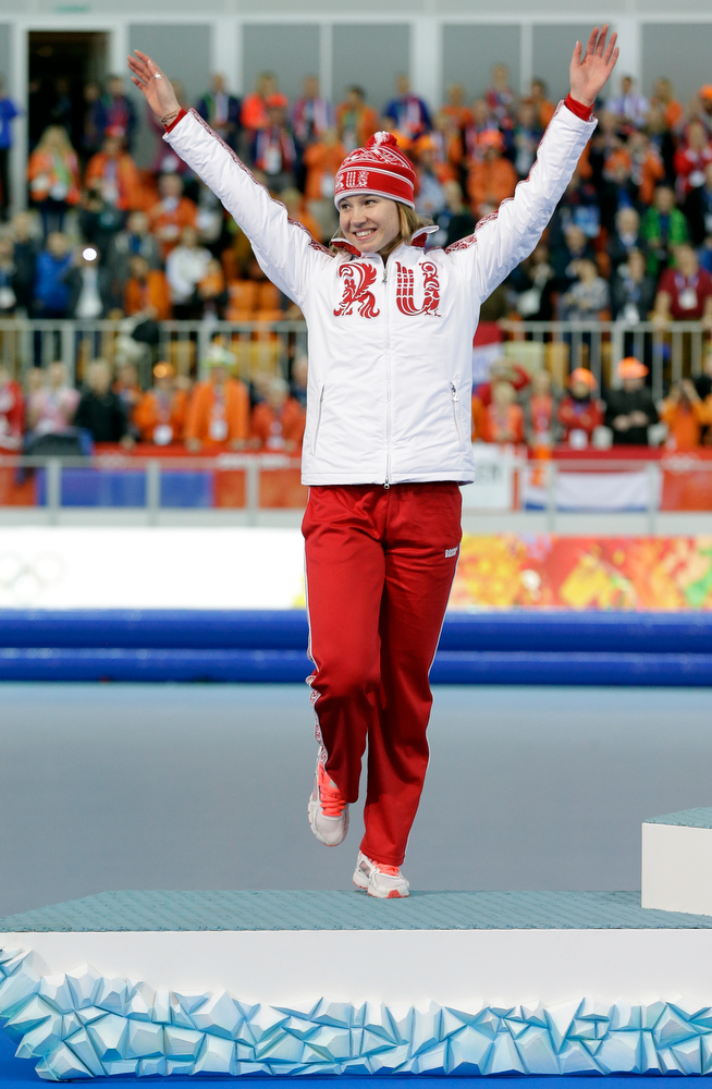 . Silver medalist from Russia\'s Olga Fatkulina jumps in celebration during the flower ceremony for the women\'s 500-meter speed skating at the Adler Arena Skating Center at the 2014 Winter Olympics, Tuesday, Feb. 11, 2014, in Sochi, Russia. (AP Photo/Patrick Semansky)