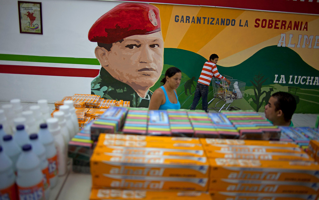 . In this April 8, 2013 photo, a mural of Venezuela\'s late President Hugo Chavez adorns a supermarket wall as customers shop in Maracay, Venezuela. Outside Venezuela\'s capital, power outages, food shortages and unfinished projects abound; important factors heading into Sunday\'s election to replace Chavez, who died last month after a long battle with cancer. Maduro, Chavez\'s hand-picked successor, is favored to win, largely on the strength of Chavez\'s generous anti-poverty programs. But recent polls show that support for Maduro may be eroding. (AP Photo/Ramon Espinosa)