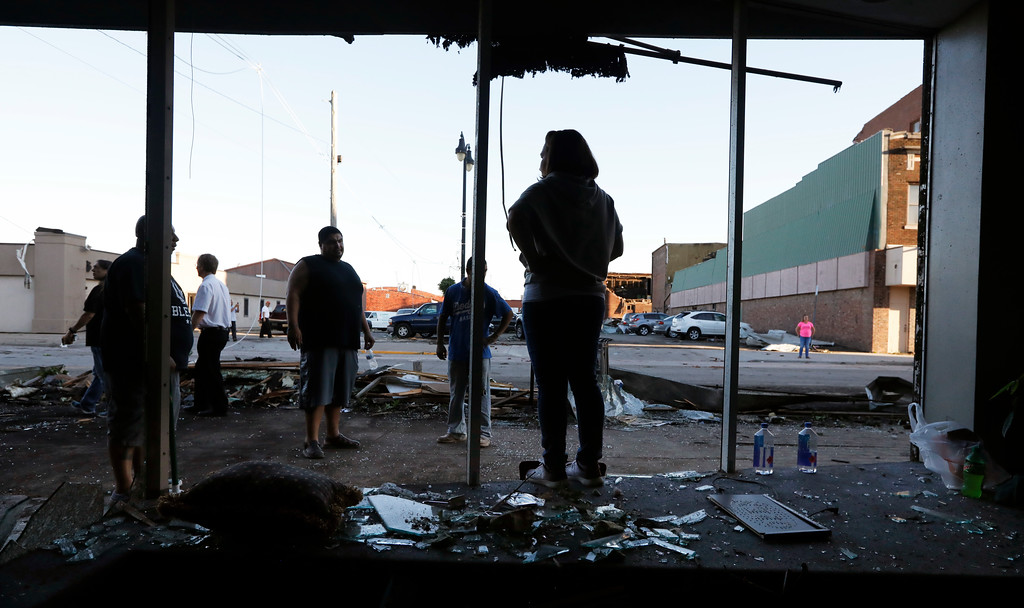 . Stephanie Moz, of Marshalltown, Iowa, center, stands in the front window of her tornado-damaged business on Main Street, Thursday, July 19, 2018, in Marshalltown, Iowa. Several buildings were damaged by a tornado in the main business district in town including the historic courthouse. (AP Photo/Charlie Neibergall)
