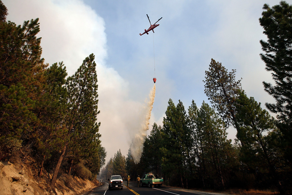. A helicopter drops water over a hot spot while battling the Rim Fire near Yosemite National Park, Calif., on Sunday, Aug. 25, 2013.  (AP Photo/Jae C. Hong)