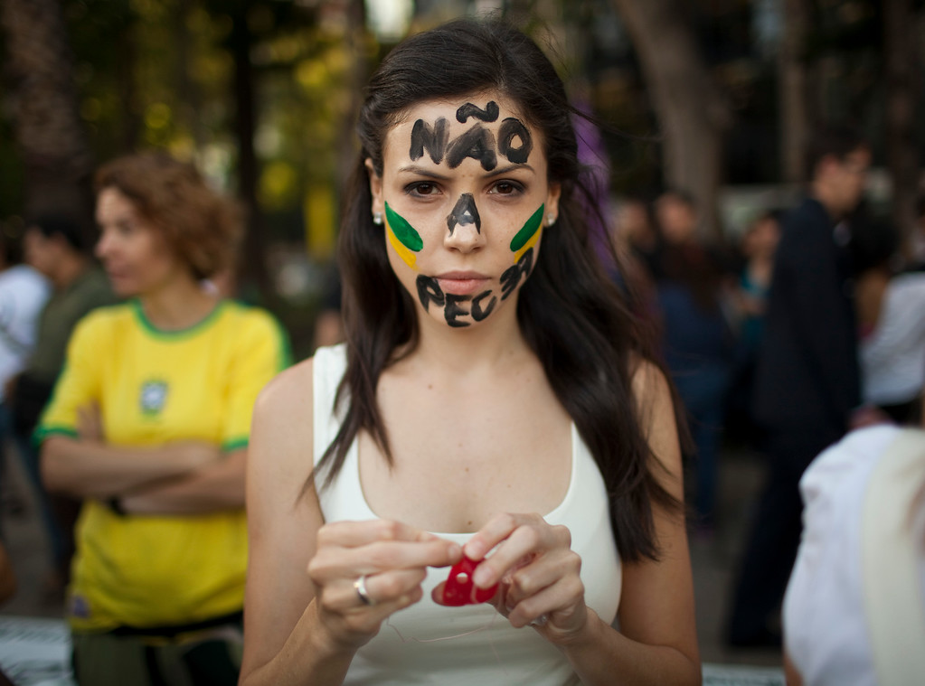 """. Marcella Santiago whose face is painted with a message in Portuguese; \""""No to PEC 37,\"""" prepares to put on a clown nose before joining protestors near the Angel of Independence monument in Mexico City, Tuesday, June 18, 2013. Brazilian nationals gathered to condemn the heavy tax burden in Brazil, corrupt politicians and woeful public education, health and transport systems. PEC 37 is a proposed constitutional amendment that limits the powers of the Public Ministry to investigate corruption and abuse. Some protestors wear a clown nose to symbolize the \""""circus\"""" that they believe Brazil politics has become. (AP Photo/Ivan Pierre Aguirre)"""