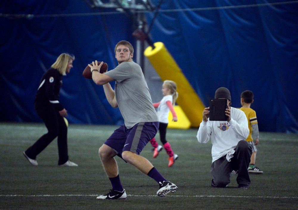 . Former Denver Broncos quarterback, Jake Plummer, right, uses a computer tablet to video former Kansas State star quarterback, Collin Klein, during passing drills inside the South Suburban Parks and Recreation\'s Sport Dome in Centennial, Colorado, Thursday morning, February 14th, 2013.  Plummer has spent weeks with Klein preparing him for the upcoming NFL Scouting Combine in Indianapolis, Indiana February 20th thru February 26th 2013. (Photo By Andy Cross / The Denver Post)