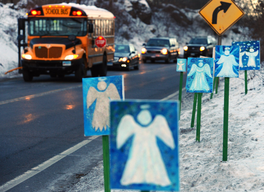 Description of . A bus traveling from Newtown, Conn., to Monroe stops in front of 26 angels along the roadside on the first day of classes for Sandy Hook Elementary School students since the Dec. 14 shooting, in Monroe, Conn., Thursday, Jan. 3, 2013. Chalk Hill School in Monroe was overhauled especially for the students from the Sandy Hook School shooting. (AP Photo/Jessica Hill)