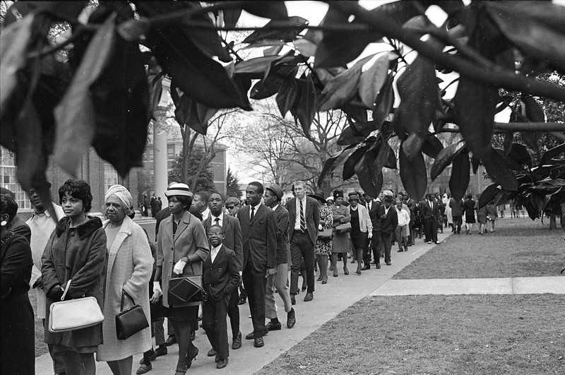 . Magnolia leaves frame some of the thousands of mourners who lined up to view the body of slain civil rights leader, Dr. Martin Luther King, Jr., in Atlanta, April 7, 1968. (AP Photo/Jack Thornell)