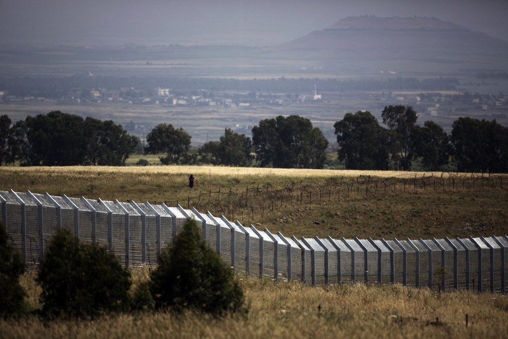 . A picture taken from the Israeli side of the border shows a Syrian woman waking near the Syria-Israel boundary fence in the Israeli annexed Golan Heights near the southern Syrian village of Ar Rafide on May 7, 2013 as fighting continues to ravage Syria. The number of Syrians displaced within their homeland by the vicious civil war has reached 4.25 million, the UN humanitarian office. MENAHEM KAHANA/AFP/Getty Images
