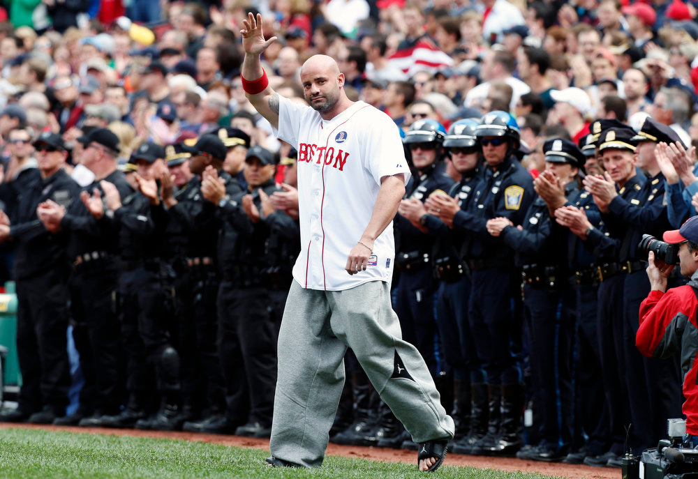 Description of . Boston Marathon bombing victim Steven Byrne waves as he comes onto the field for a ceremonial first pitch before a baseball game between the Boston Red Sox and the Kansas City Royals in Boston, Saturday, April 20, 2013. (AP Photo/Michael Dwyer)