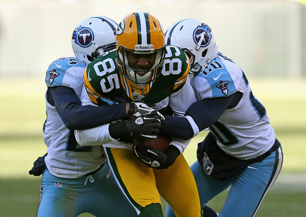 . Greg Jennings #85 of the Green Bay Packers hangs onto the ball as he is hit by Coty Sensabaugh #24 (L) and Alterraun Verner #20 of the Tennessee Titans at Lambeau Field on December 23, 2012 in Green Bay, Wisconsin. The Packers defeated the Titans 55-7. (Photo by Jonathan Daniel/Getty Images)