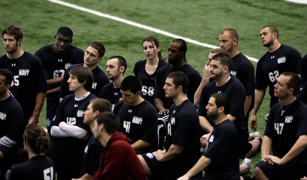 . Lauren Silberman, top center, kneels on the indoor turf before kicker tryouts at the NFL football regional combine workout on Sunday, March 3, 2013, in Florham Park, N. J.(AP Photo/Mel Evans)