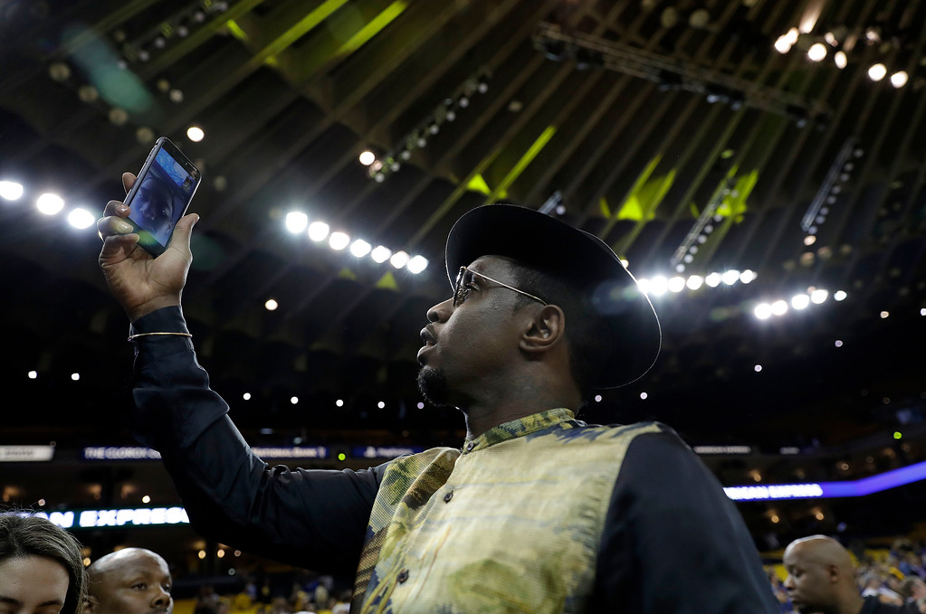 ". Musician Sean ""Diddy\"" Combs checks his phone before Game 5 of basketball\'s NBA Finals between the Golden State Warriors and the Cleveland Cavaliers in Oakland, Calif., Monday, June 12, 2017. (AP Photo/Marcio Jose Sanchez)"