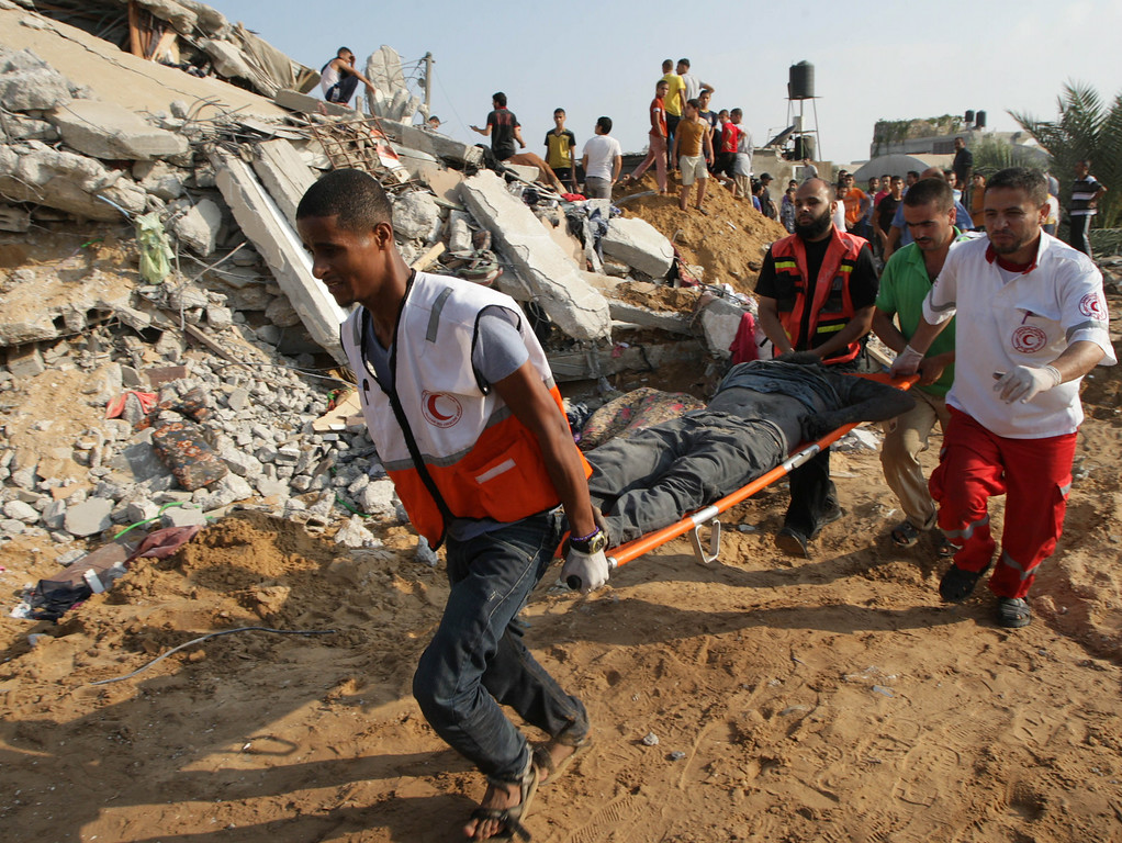 . Palestinian rescue workers carry the body of a member of Duheir family, after removing it from under the rubble of a building destroyed by an Israeli air strike in Rafah on July 29, 2014, in the southern of Gaza strip. Bloodshed in war-torn Gaza surged with dozens more Palestinians killed as the conflict raged into a fourth week and Iran accused Israel of genocide in the tiny enclave.  AFP PHOTO/ SAID  KHATIB/AFP/Getty Images