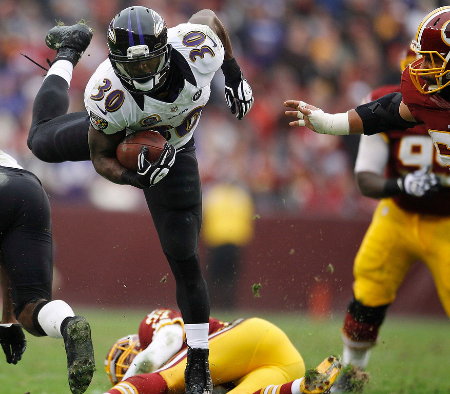 . Baltimore Ravens running back Bernard Pierce (L) leaps through the Washington Redskins defense in the first half of their NFL football game in Landover, Maryland December 9, 2012. REUTERS/Gary Cameron (UNITED STATES - Tags: SPORT FOOTBALL)