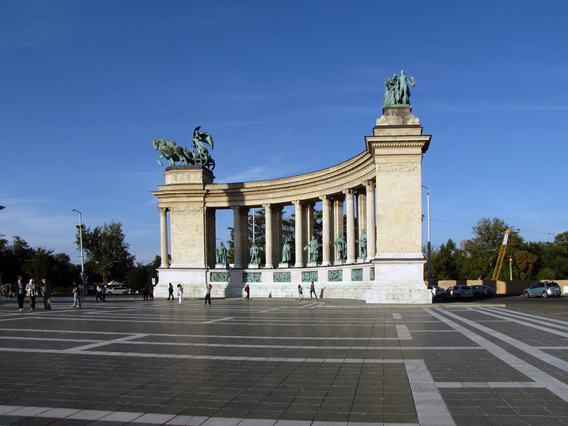 96-A colonnade encompasses the central column. Each wing holds 7 statues of Hungarian kings or heroes. This is the right wing of the monument. Sculptures at the top corners are Peace (left) and Knowledge and Glory (far right).
