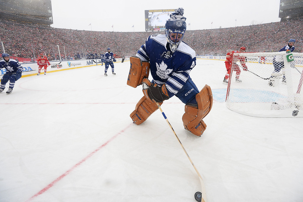 . Goaltender Jonathan Bernier #45 of the Toronto Maple Leafs plays the puck behind the net in the first period against the Detroit Red Wings during the 2014 Bridgestone NHL Winter Classic on January 1, 2014 at Michigan Stadium in Ann Arbor, Michigan.  (Photo by Jamie Sabau/Getty Images)