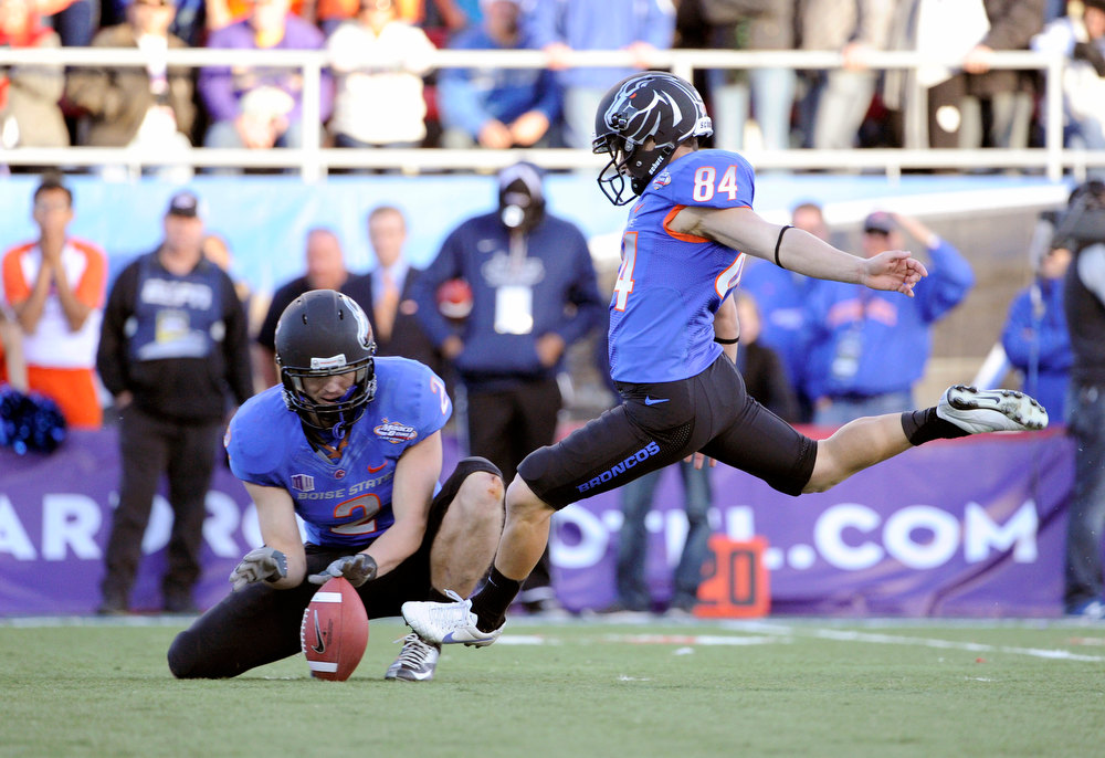 Description of . Boise State Matt Miller (2) holds the ball for kicker Michael Frisina (84) who boots the ball during the final minutes of the MAACO Bowl NCAA college football game on Saturday, Dec. 22, 2012, in Las Vegas. The field goal was the go-ahead for Boise State to defeat Washington 28-26. (AP Photo/David Becker)