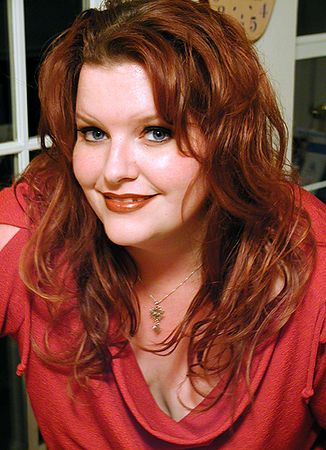 """Kitchen at night, January 2004.  Okay, maybe not as """"candid"""" as usual.  I did have her lean forward, bearing down on the countertop.   But she looked like this, so I took her picture."""