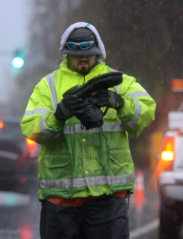 . Michael Martinez, with the Emeryville Deptartment of Public Works, empties his shoe as he does traffic control on a flooded section of Powell Street in Emeryville, Calif., on Thursday, Dec. 11, 2014. (Kristopher Skinner/Bay Area News Group)