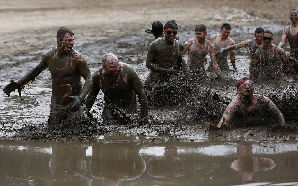""". Participants of the \""""Tough Mudder\"""" endurance event series run through the \""""mud-mile\"""" obstacle in the Fursten Forest, a former British Army training ground near the north-western German city of Osnabrueck July 13, 2013. The hardcore but un-timed event over 16 km (10 miles) was designed by British Special Forces to test mental as well as physical strength. Some 4,000 competitors had to overcome obstacles of common human fears, such as fire, water, and heights.   REUTERS/Wolfgang Rattay"""