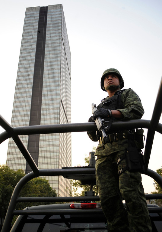 . A soldier stands guard near the headquarters of state oil giant Pemex in Mexico City January 31, 2013. A powerful explosion rocked the Mexico City headquarters of state oil giant Pemex on Thursday, killing at least 14 people and injuring 100 others.   REUTERS/Alejandro Dias