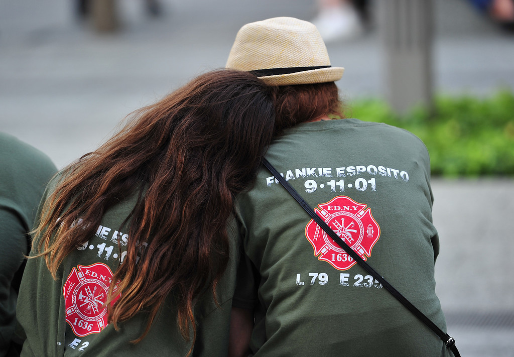 . Two people with shirts commemorating New York City Fire Department firefighter Frankie Esposito sit at the South Tower reflecting pool of the 9/11 Memorial during ceremonies for the twelfth anniversary of the terrorist attacks on lower Manhattan at the World Trade Center site on September 11, 2013 in New York City.  (Photo by Stan Honda-Pool/Getty Images)